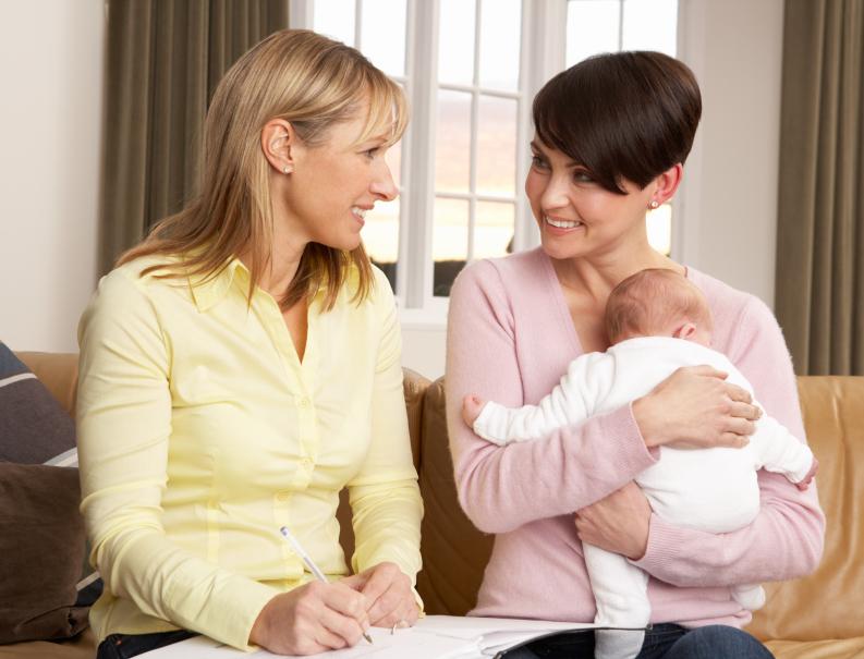 Hebamme mit Mutter und Neugeborenen auf der Couch